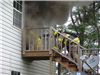 Firefighters Climb Steps to Get into Burning Structure